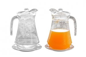orange juice and water in pitcher on plate